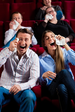 Couple and other people, probably friends, in cinema watching a movie; it seems to be a funny movie photo