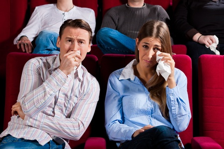 Couple and other people, probably friends, in cinema watching a movie; it seems to be a sad movie photo