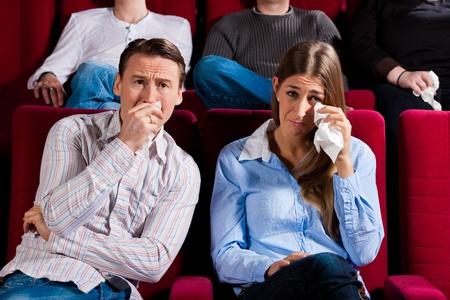teatro: Pareja y otras personas, probablemente sus amigos, en el cine viendo una pel�cula, sino que parece ser una pel�cula triste
