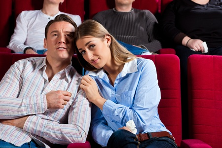 Couple and other people, probably friends, in cinema watching a movie; it seems to be a romantic movie photo