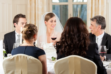 Wedding party at dinner - the bridal couple is clinking glasses with wine photo