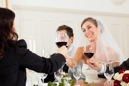 clinking: Fiesta de la boda en la cena - la pareja de novios se tintineo vasos con el vino