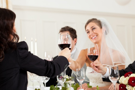 Wedding party at dinner - the bridal couple is clinking glasses with wine Stock Photo - 12443389