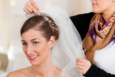 Stylist pinning up a bride s hairstyle and bridal veil before the wedding photo