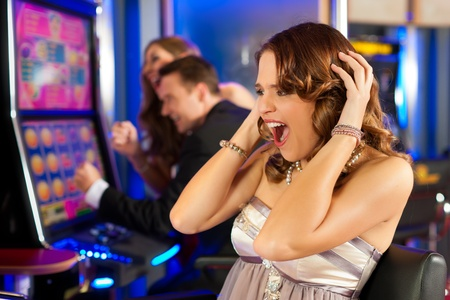 Friends in Casino on a slot machine; the woman in front obviously is loosing Stock Photo - 12443499
