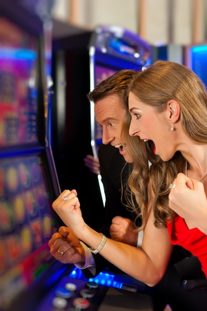gambling chip: Couple in Casino on a slot machine winning and having fun Stock Photo