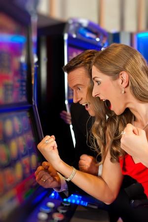 tragamonedas: Pareja en el casino en una máquina tragamonedas ganar y divertirse