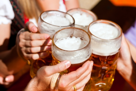 Four friends with a fresh beer in a Beer garden; close-up on beer stein Stock Photo