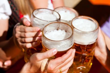 Vier vrienden met een frisse pint in een biergarten, close-up op bier stein