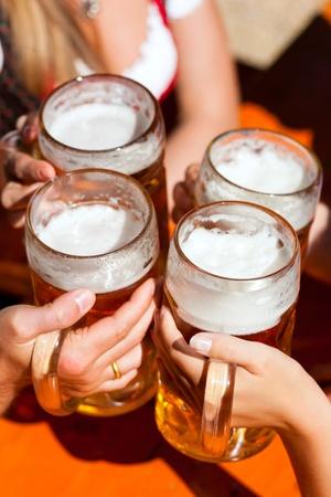 Vier Freunde mit einem frischen Bier in einem Biergarten, close-up auf Bierkrug