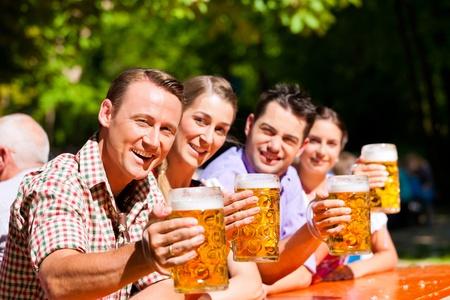 hombre tomando cerveza: Dos feliz pareja sentada en el jard�n de la cerveza y disfrutar de la cerveza y el sol