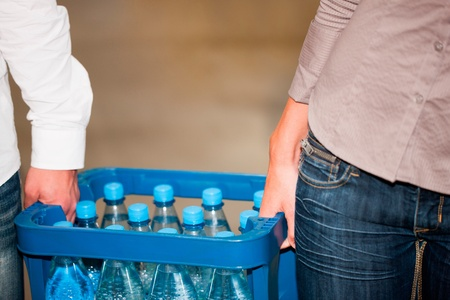 beverage display: Young couple in supermarket buying beverages together, close-up on box