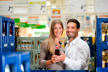 Young couple shopping together at supermarket and looking for groceries Stock Photo - 12443629