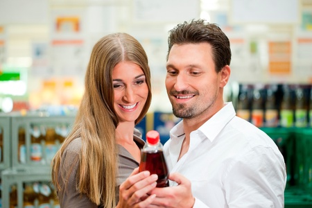 Young couple in supermarket buying beverages together Stock Photo - 12443625