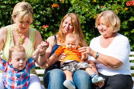 Two young, happy mothers sitting with their children and their grandmother in a park outdoors on blanket and play with their children Stock Photo - 12443628