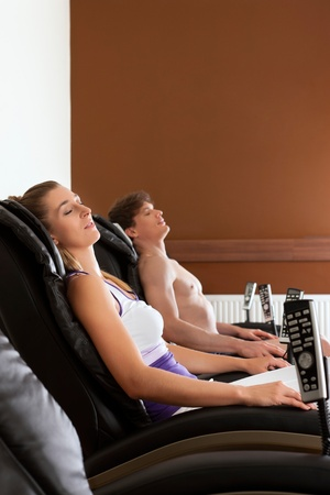 asleep chair: Young couple is recovering on massage chair in gym after exercising for their fitness Stock Photo