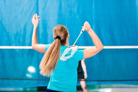 Women playing Badminton and doing sport in gym Stock Photo - 12443411