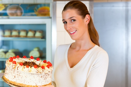 torte: Female baker or pastry chef with torte in bakery Stock Photo