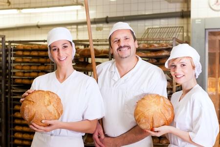 Baker stand mit seinem Team in der B�ckerei mit frisch gebackenem Brot
