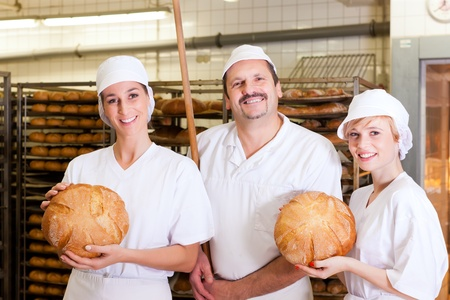 Baker standing with his team in bakery with freshly baked bread photo
