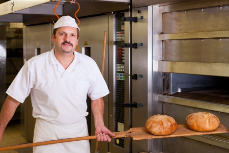 Male baker baking fresh bread in the bakehouse photo