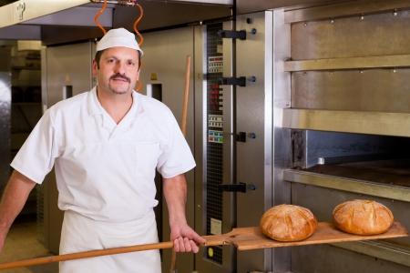 bread shop: Maschio fornaio pane fresco nel forno