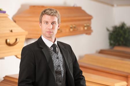 Undertaker dans son magasin avec un écran de cercueils