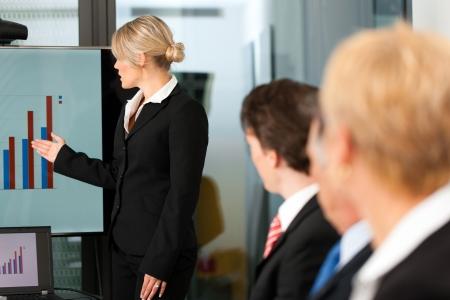 Negocios - reunión del equipo en una oficina con computadora portátil, el jefe con sus empleados Foto de archivo