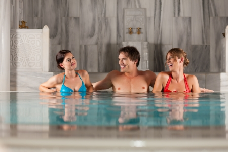 Three friends - one man and two women - in swimming pool or thermal bath doing wellness photo