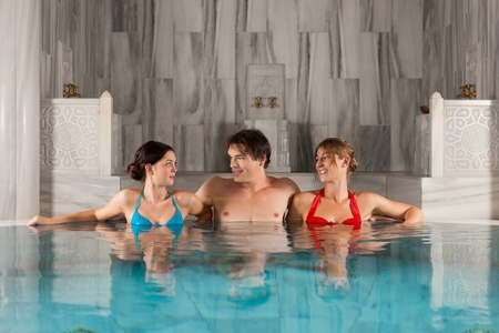 turkish woman: Three friends - one man and two women - in swimming pool or thermal bath doing wellness