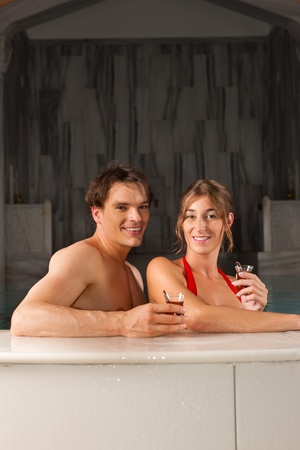 wife of bath: couple drinking tea in swimming pool; they doing wellness in their vacation