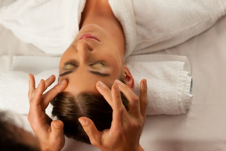 Young woman enjoying head massage or cosmetic treatment in Spa Stock Photo - 12718730