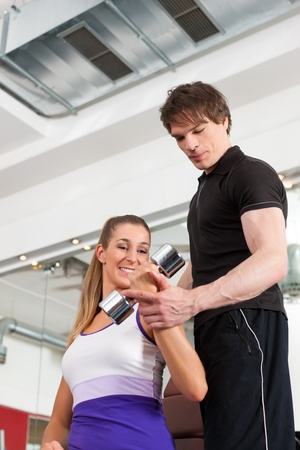 sportive: Young couple exercising in gym with weights, one of them is personal trainer