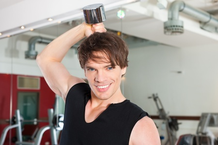 strengthen: Young man is exercising with barbell in gym to strengthen the muscles