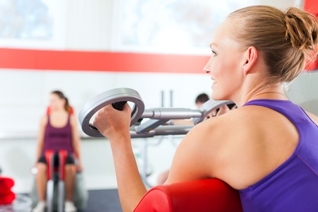 woman lifting weights: Happy, young women doing strength or sports training in gym for a better fitness Stock Photo