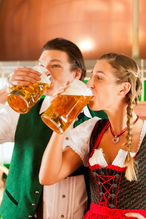 steins: Young man and woman in traditonal Tracht with beer glass in brewery, in front of brewing kettle