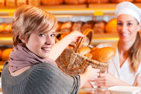 selling service: Female baker or saleswoman in her bakery with a female customer and fresh pastries or bakery products