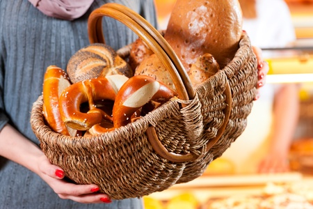 breadbasket: Female customer standing with breadbasket and fresh bread and rolls in bakery Stock Photo