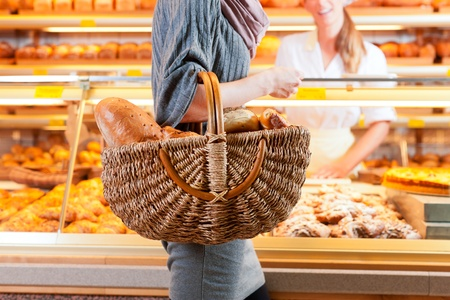 Female customer standing with breadbasket and fresh bread and rolls in bakery photo