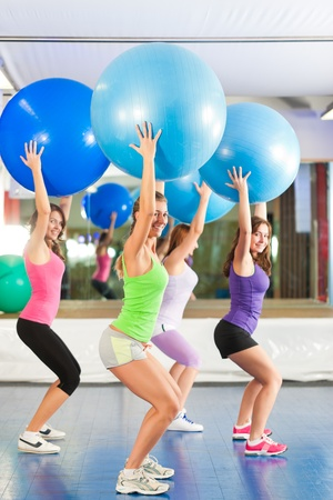Fitness - Young women doing sports training or workout with gymnastic ball in a gym Stock Photo - 12718792