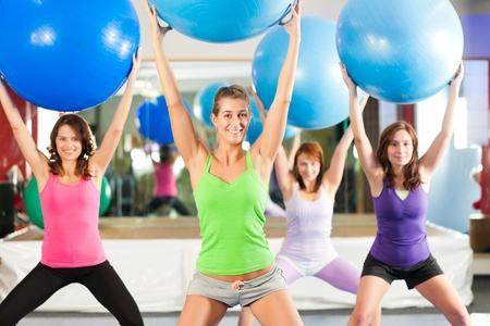 Fitness - Young women doing sports training or workout with gymnastic ball in a gym Stock Photo - 12718707