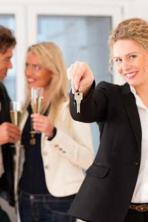 Real estate market - young couple looking for real estate to rent or buy; they celebrate with champagne and get the keys Stock Photo - 12718710