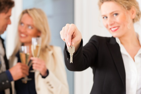 Real estate market - young couple looking for real estate to rent or buy; they celebrate with champagne and get the keys Stock Photo - 12718542