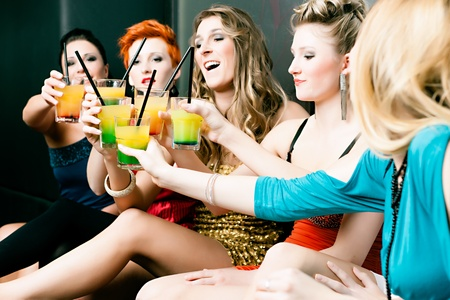 cocktaildress: Vrouwen of modellen in club of disco drinken van cocktails met plezier