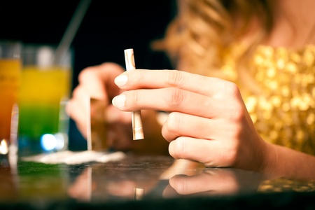 Young woman snorting cocaine with a bill, close-up photo