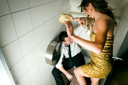 toilette: Young couple fighting on a party in the toilette, he is obviously drunk Stock Photo