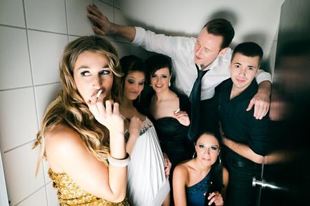 drogadiccion: La gente en el club y mucho fumar un cigarrillo en la taza del ba�o y tienen de diversi�n Foto de archivo