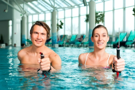 water aerobics: Fitness - a young couple  man and woman  doing sports and gymnastics or water aerobics under water in swimming pool or spa with Nordic walking sticks