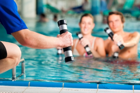 Fitness - a young couple man and woman doing sports and gymnastics or water aerobics under water in swimming pool or spa with dumbbells and instructor