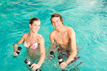 Fitness - a young couple man and woman doing sports and gymnastics or water aerobics under water in swimming pool or spa with dumbbells